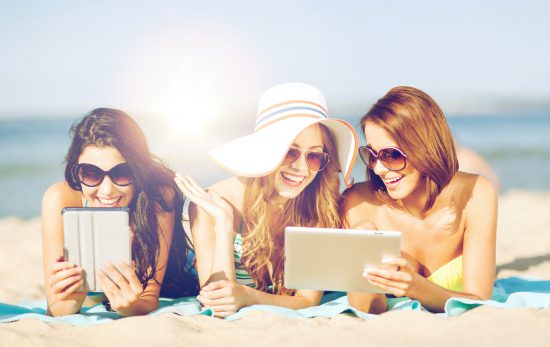 Friends on the beach with tablets from shutterstock